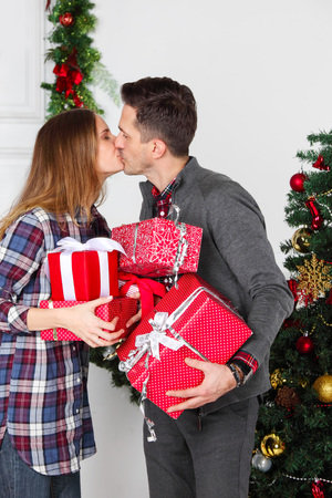 Couple in love standing next to a nicely decorated Christmas tree, holding Christmas gifts and kissing Stock Photo