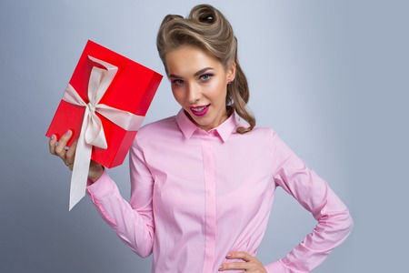 Happy beautiful funny woman holding red gift box with white ribbon Archivio Fotografico - 115176494