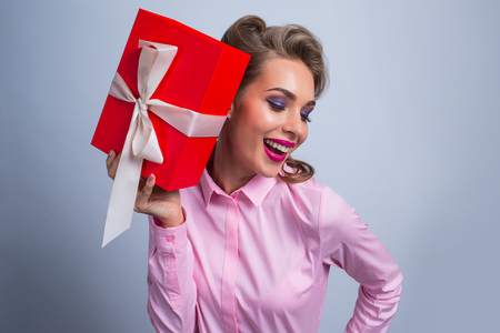 Happy beautiful funny woman holding red gift box with white ribbon Banque d'images
