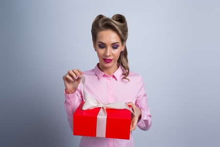 Happy beautiful funny woman open red gift box with white ribbon