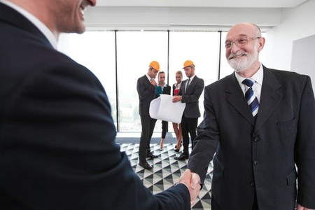 Business people shaking hands at meeting of architects and investors in office
