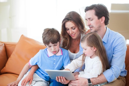 Portrait of happy family with two children sitting on sofa and using digital tablet pc 写真素材