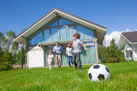 Famille avec enfants jouant au football sur la pelouse du jardin près de leur maison