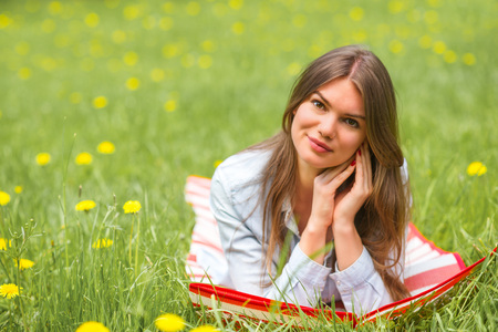 Beautiful young woman laying on grass with dandelion flowers in park Stock Photo