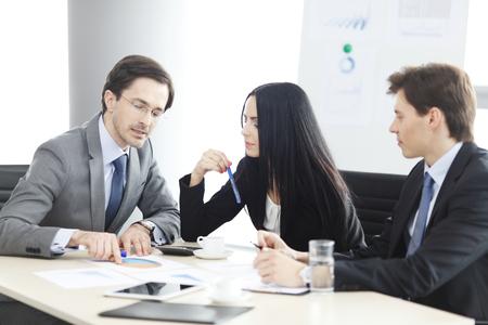 Gente de negocios discutiendo informes financieros durante una reunión