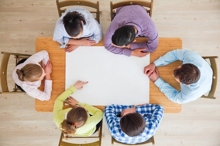 Hipster business teamwork brainstorming planning meeting concept, people team sitting around the table with white paper and pointing, copy space