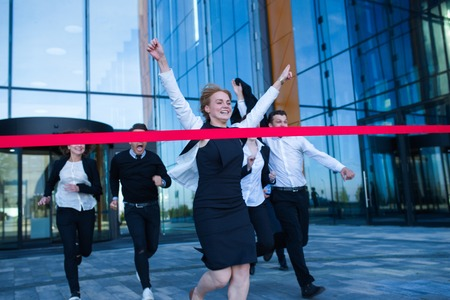 Group of happy business people running from office building crossing red ribbon finish line