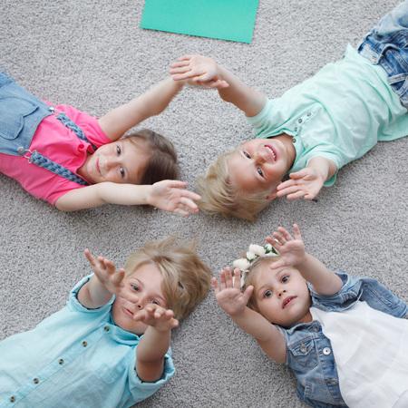 Groep gelukkige jonge geitjes tot op vloer, bovenaanzicht Stockfoto
