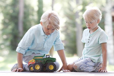 Little brothers playing with toy cars outdoors 写真素材
