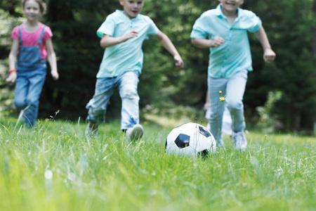 Bambini felici che giocano a calcio nel parco estivo Archivio Fotografico