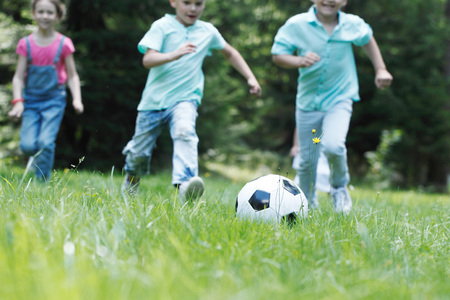 Happy children playing football in summer park Imagens