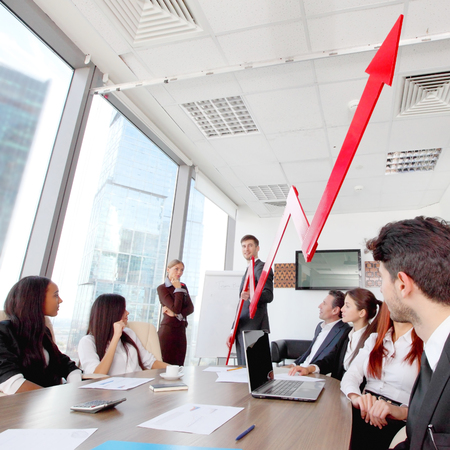 Business people discuss red arrow of income growth at meeting