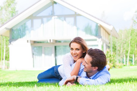 Happy smiling couple laying down in their home garden Imagens