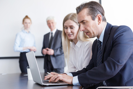 Business people working with laptop together in office