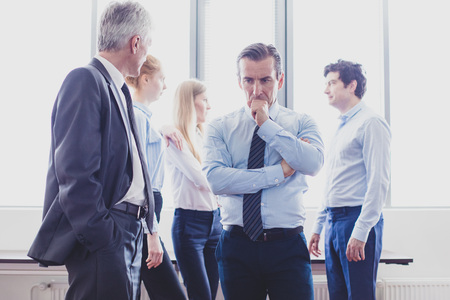 Colleagues having business conversation at meeting in office, serious man thinking holding chin