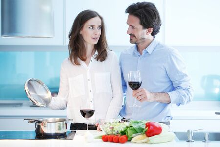 Portrait of a couple having a glass of red wine while cooking dinner of fresh vegetables