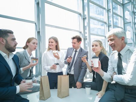 Business people having coffee break eating donuts together in office
