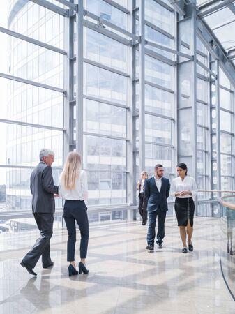 Gens d'affaires marchant dans un hall moderne d'immeuble de bureaux Banque d'images