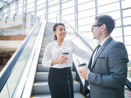 Businessman and businesswoman standing together on escalator and talk about business holding coffee in hand