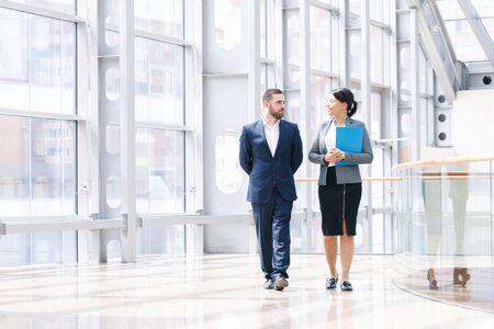 Un homme d'affaires et une femme d'affaires marchent ensemble et parlent d'affaires tenant un café à la main Banque d'images