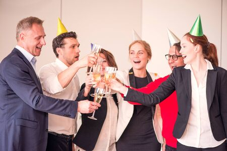 People in business outfit celebrating something in the office clinking glasses of champagne Imagens