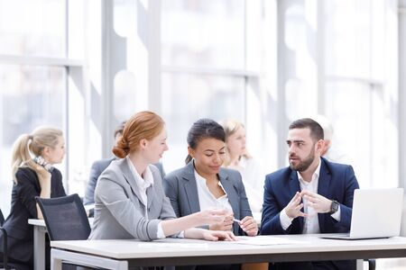 Business team sitting by the table with laptop and documents in office Stock Photo