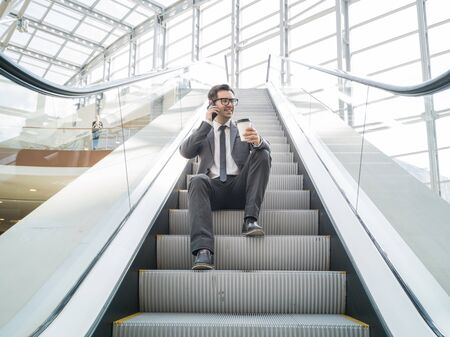 Businessman sitting on escalator talking on phone and holding coffee in hand