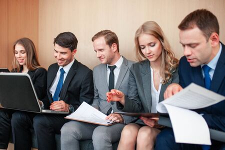 Business people working together sitting in a row in lobby and holding laptop and documents on knees Stock Photo