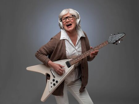 Happy funny senior woman playing electric guitar Stock Photo