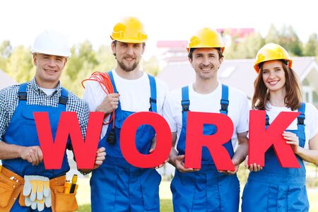 Portrait of happy smiling construction workers team with red work letters