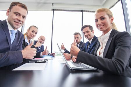 Happy business team having a meeting at office table, showing OK with thumbs up