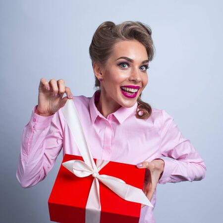 Happy beautiful funny woman unpacks holiday gift in red box
