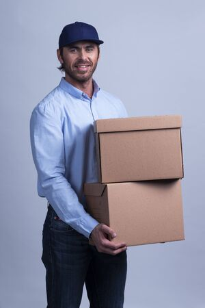 Delivery man carrying cardboard box on gray background