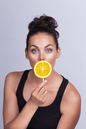 Portrait of beautiful woman with perfect skin holding orange slice on stick
