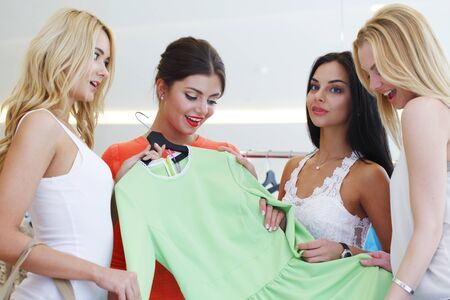 Young happy women choosing dress on sale in shopping mall