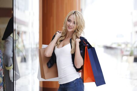 Woman with paper bags looking at showcase in shopping mall Stockfoto