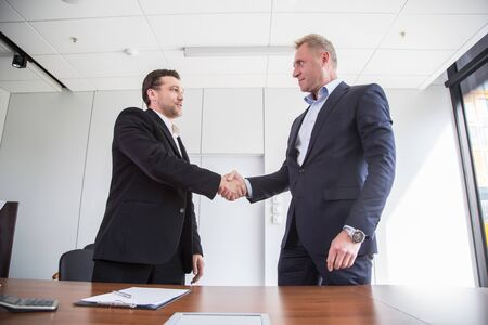 Business people in formal wear sign contract and shaking hands
