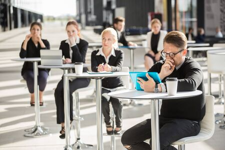 Lot of business people sitting in cafe of modern office building