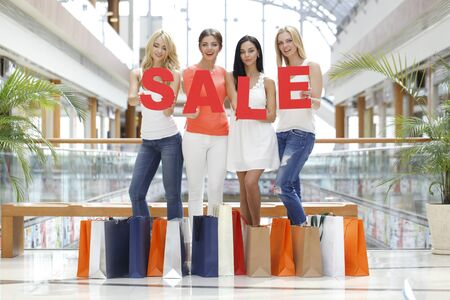 Women with big red sale letters in mall, shopping concept
