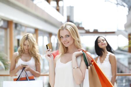 Young beautiful happy women with shopping bags and golden credit card in mall Imagens