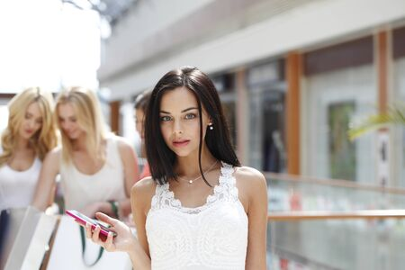 Young beautiful happy women with shopping bags and cellphone in mall
