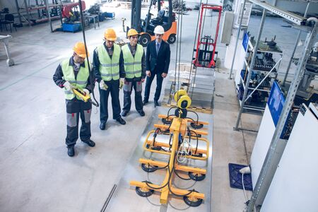 Workers near metal sheet lifting device at factory