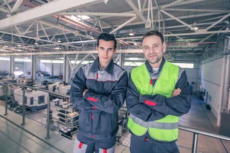 Team of two workers in uniform standing at background of CNC factory 写真素材