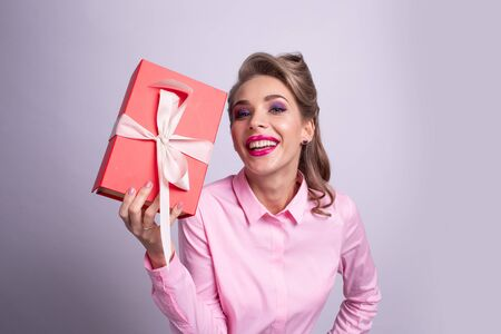 Happy beautiful funny woman holding red gift box with white ribbon 写真素材