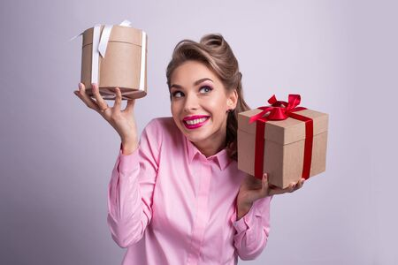 Young woman puts her ear to the presents with bows