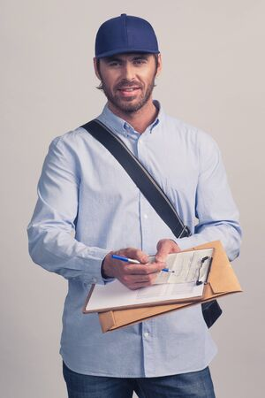 Man in blue uniform holding delivery form on clipboard for delivery