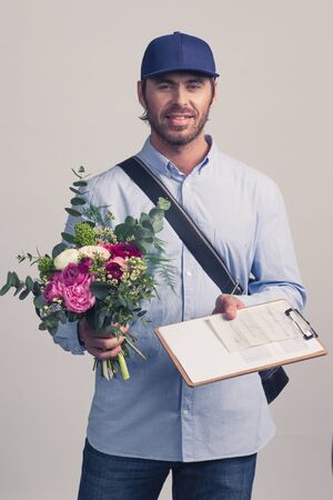 Delivery man holding flower bouquet and form