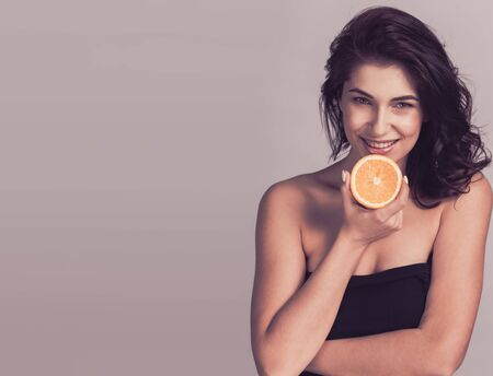 Fashion portrait of beautiful mid adult woman holding orange copy space for text