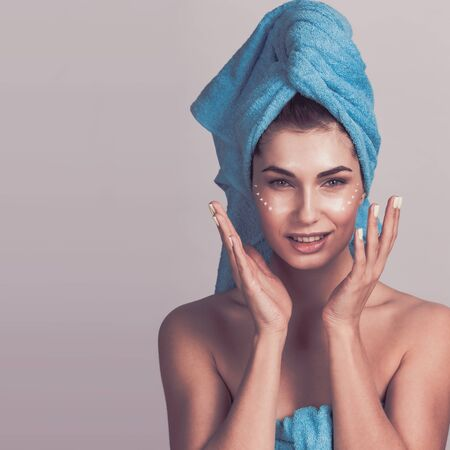 Beautiful woman with towel on head applying creme after shower