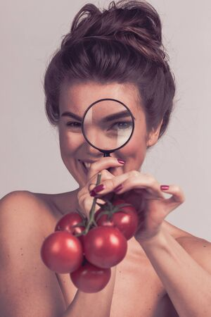 Young beautiful woman female inspecting testing tomato food with magnifying glass